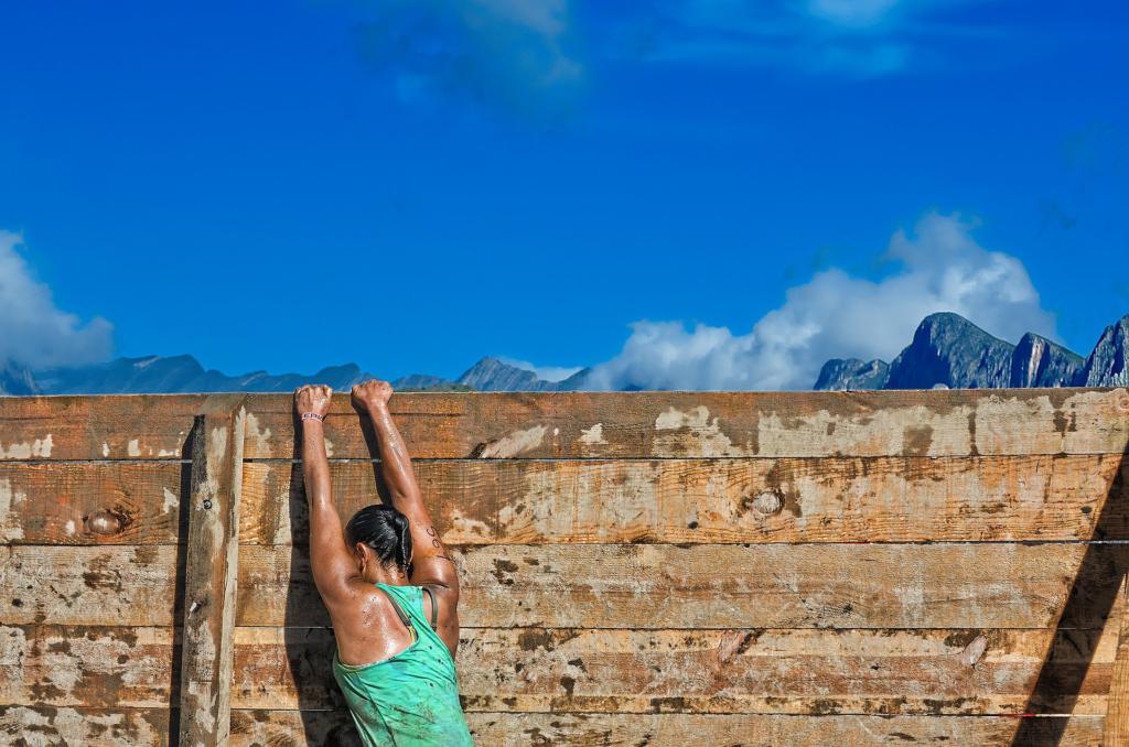 trans.SCRIPT überwindet Kommunikationsbarrieren; symbolisch klettert eine Frau über eine Wand, um in die dahinterliegende Schönheit der Natur zu gelangen